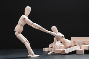 One posable wooden figure helps another in a pickle